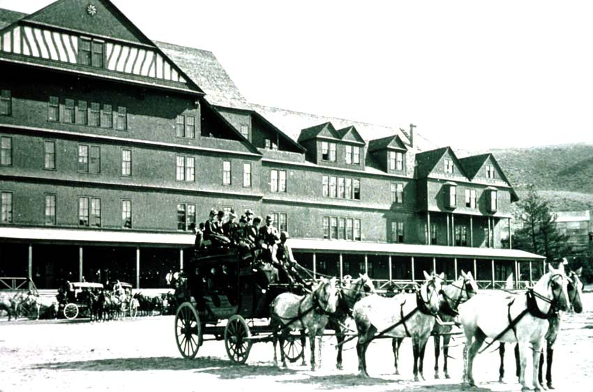 Black and White photo of people posing on a non-moving stage coach pulled by 6 horses with a large building in the background.