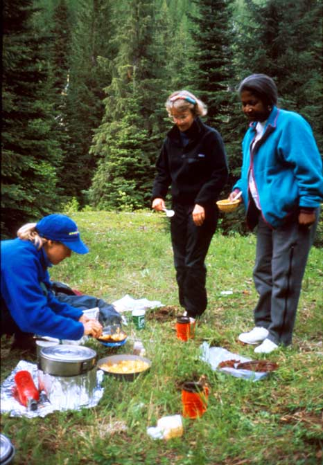 Three women preparing a backcountry meal in a small meadow surrounded by tall forest trees.