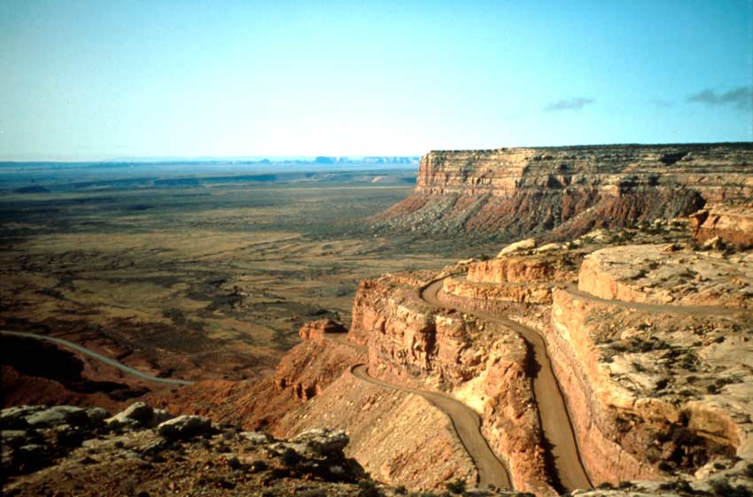 Looking out at the vertical edge of a large plateau, a dirt road winding down the face, to the valley floor below.