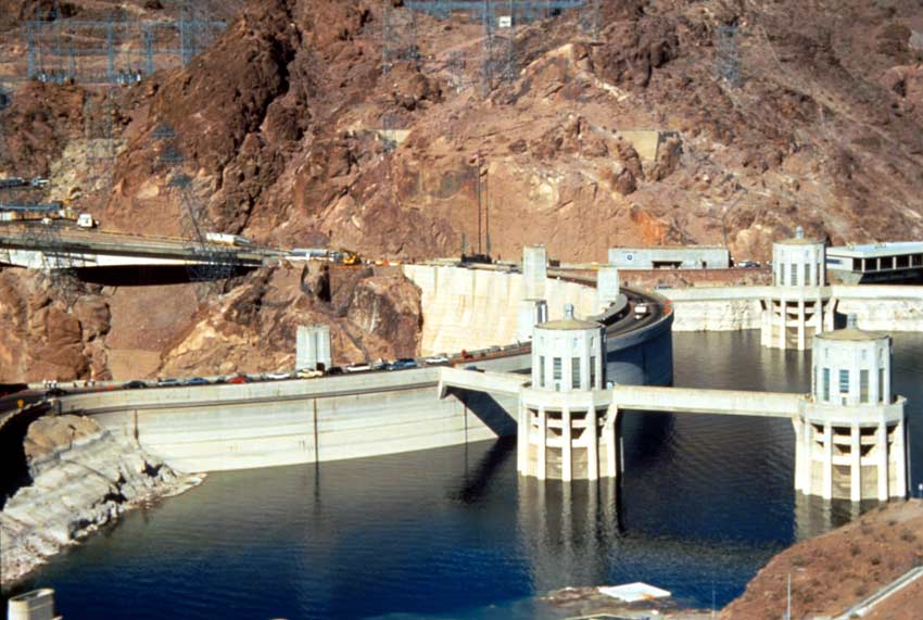 Looking into the Hoover Dam, a small string of cars moving along the top, above the dark blue water.