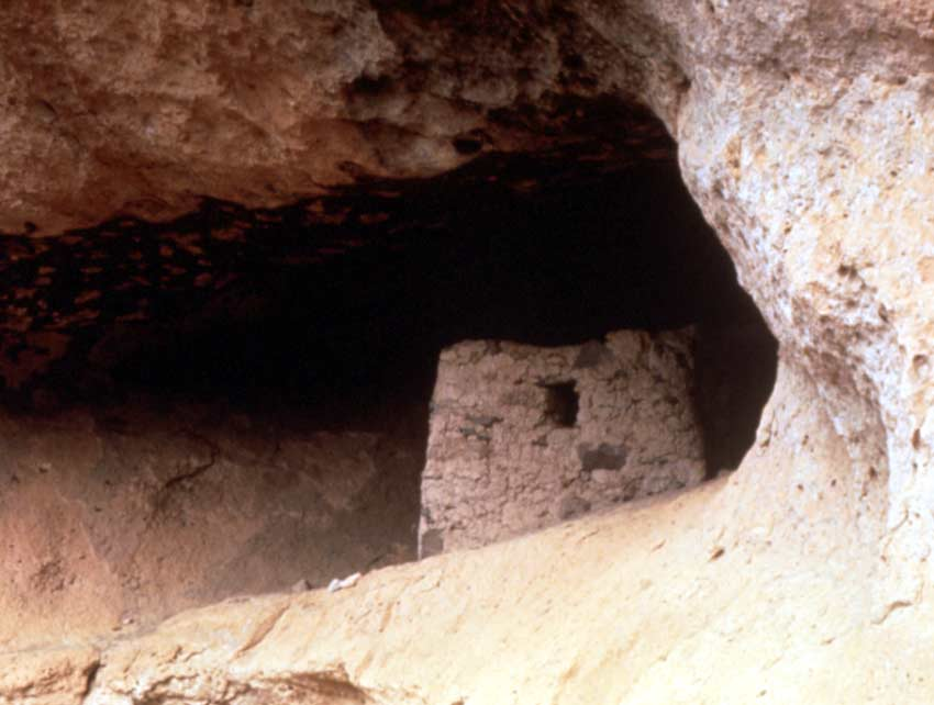 Looking into the mouth of a large cave, an ancient dwelling sitting near the entrance.