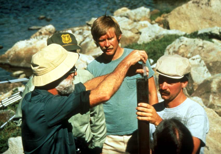 A small group of several men, analyzing a water sample.