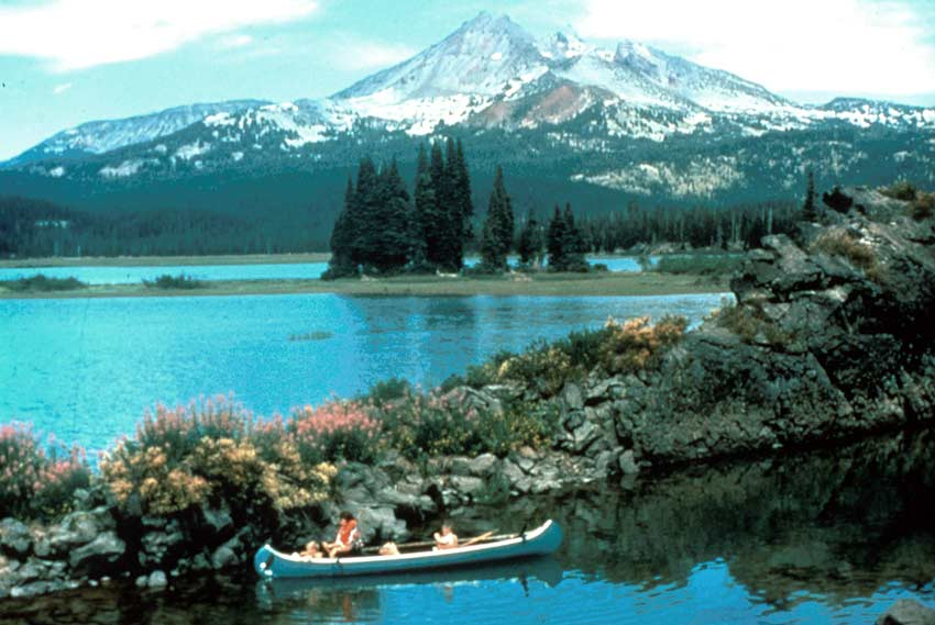 A blue canoe is paddled along a rocky point, with a tall snow-covered mountain rising from the forest beyond the lake.