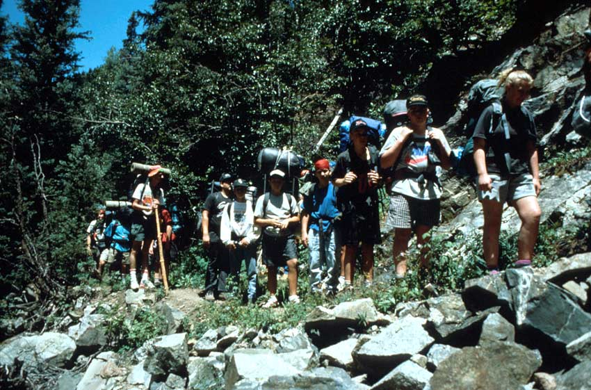 A group of backpackers traverse a rocky section of trail, along the edge of the forest.