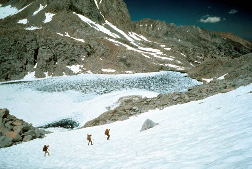Three mountaineers with large packs, traverse an alpine snowfield above a frozen lake. Rugged mountain peaks rise all around, under a deep blue sky.