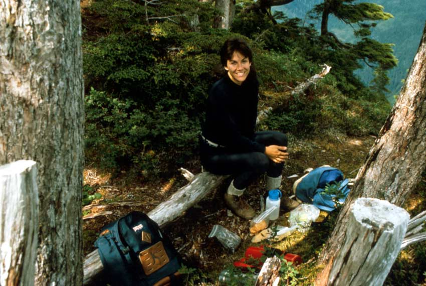 A woman sitting on a log, taking a lunch break along a forest trail.