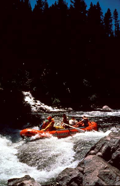 A bright red raft at the lip of a large rocky rapid, dark forest trees rising in the background.