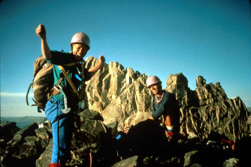 Two rock climbers loaded with gear, triumphantly raising their hands at the top of a climb, jagged rocky pinnacles rise in the background under an empty blue sky.