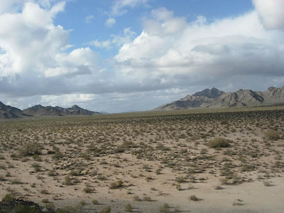 Huge clouds pass across the sky and in the distance of the shot mountains encircle the flatlands.