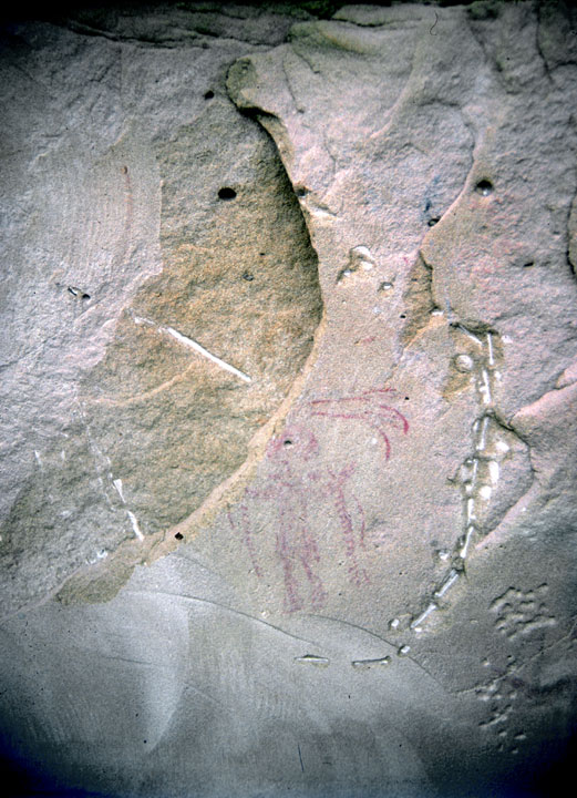 An ancient drawing on a smooth slab of stone, surrounded by various grooves and marks.