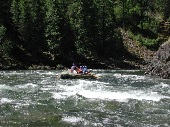 A small group of people in a green raft, shooting a section of rapids on a narrow river channel.