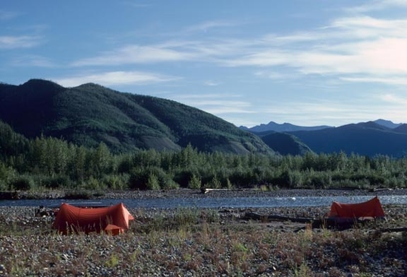 Two tents are pitched near the edge of the Tatonduk River. The river and the campers are dwarfed by the rolling mountains in the background.