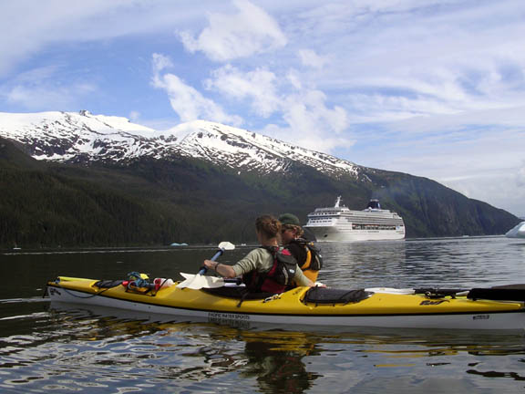 Kayak rangers paddle across the water in the Tracy Arm of the Tracy Arm - Ford's Terror Wilderness, while a large cruise ship navagates the water in the background.