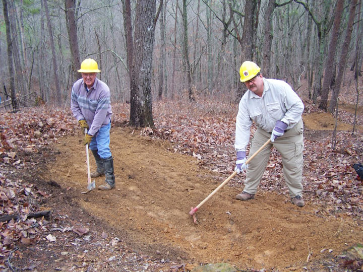 Two men working with hand tools to restore a section of forest floor.