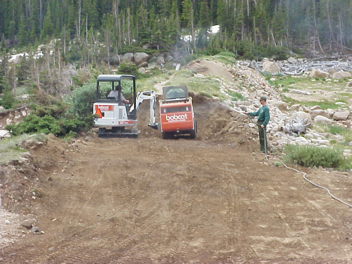 A man standing next to two small pieces of equipment, clearing away a large mound of earth.