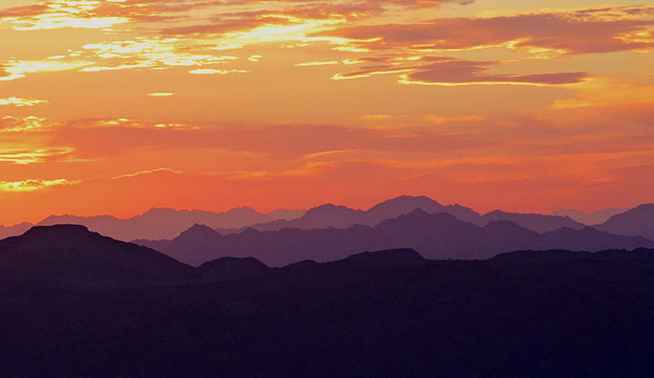 Multiple purple mountain ranges bathed in an orange sunset