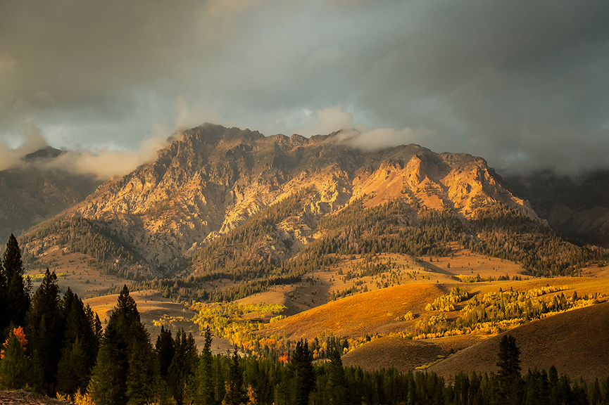 Sunlight highlights autumn foliage in a valley with clouded mountains behind it.