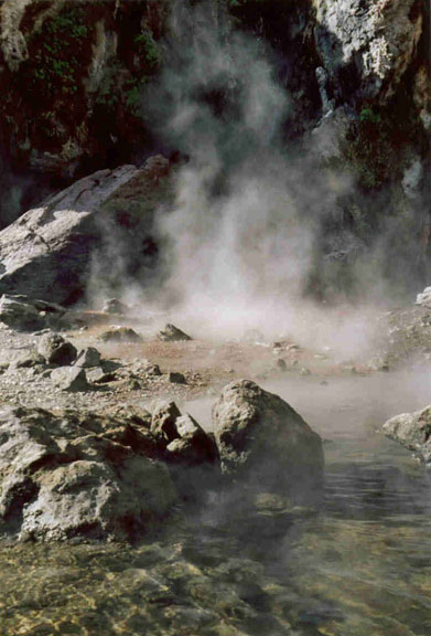 Heavy white steam rising from a clear rocky pool, against deep shadow on the high rocky wall in the background.