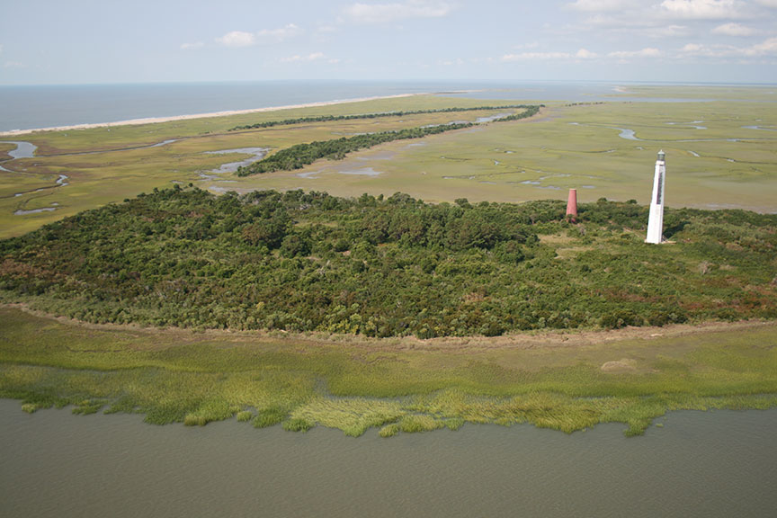 An aerial view of an island with a tall white lighthouse on it