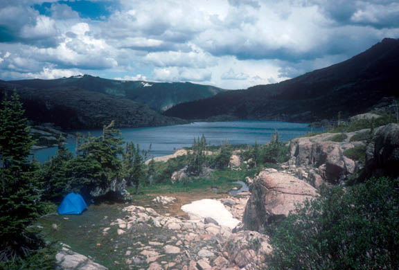 An example of at-large camping, inside Rocky Mountain National Park. The campsite is near the edge of a lake where pine trees and large boulders make their home.
