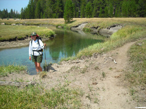 A backpacker poses next to a calm, shallow creek in the Yosemite Wilderness on a clear sunny day.