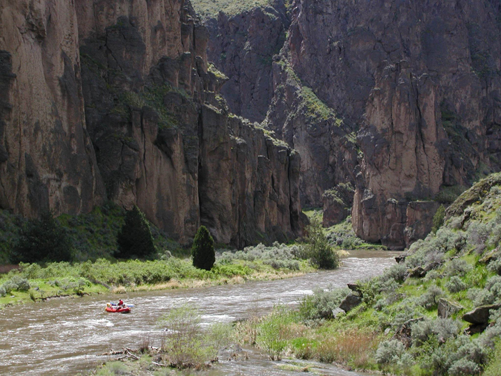 A rafter floats down a river surrouned by tall canyon walls scattered with lush green vegetation.