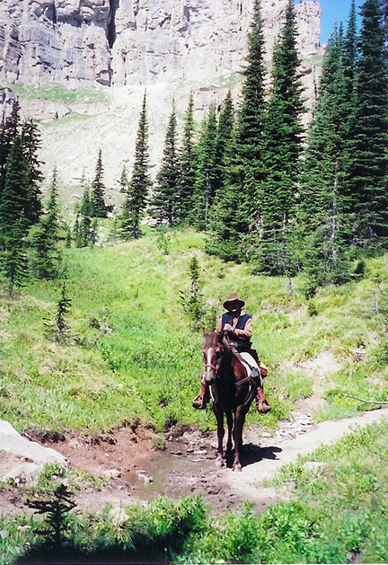A horse and rider stand in front of tall rock cliffs
