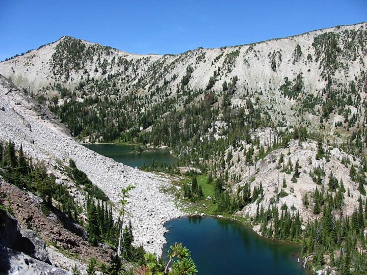 A steep alpine bowl dotted with green trees, cradling two small lakes below, surrounded by white rock.
