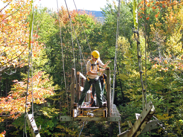 White Mountain National Forest Trail Crew disassembles a 180' suspension bridge from the Pemigewasset Wilderness in the White Mountains of NH during the autumn transition.