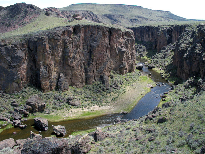 A sagebrush covered hill slopes down to a river below with steep cliffs on the opposite side.