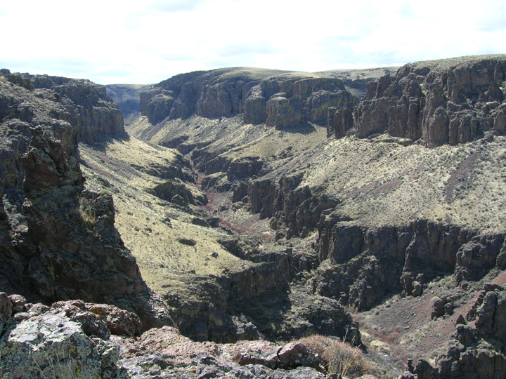 A desert landscape gives way to a canyon inside a canyon with large rocky cliffsides.