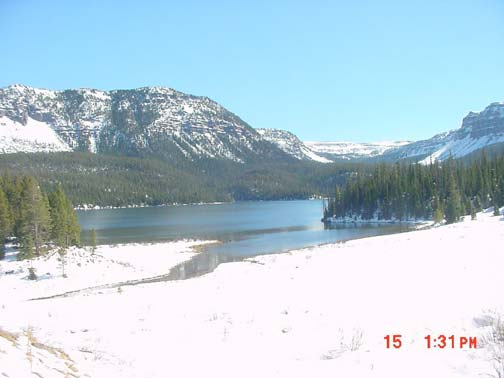 A winter landscape, looking towards a large lake, the blue water bordered by dense forest, and low mountains laced with snow.