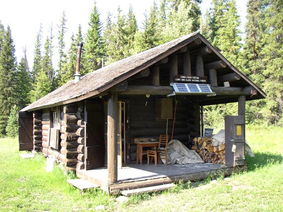 A small log cabin in the middle of a clearing, surrounded by dense forest trees.