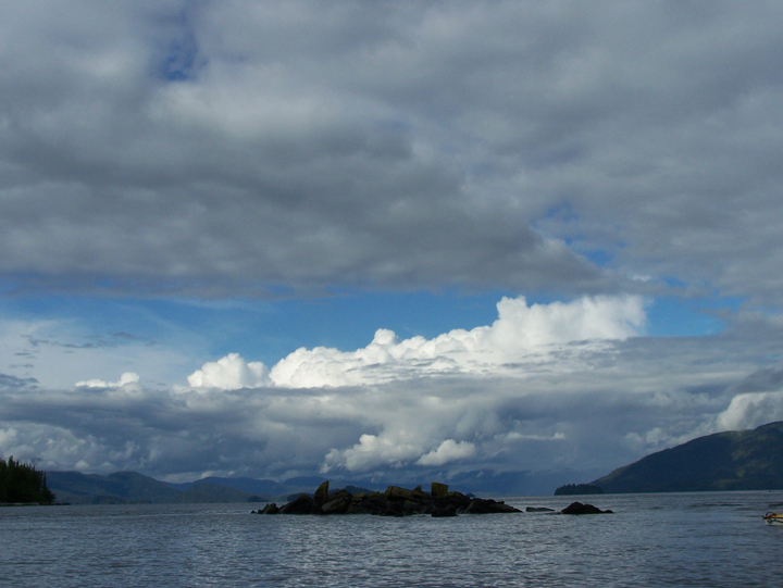A small island sits in the middle of a large body of water with masses of white puffy clouds above.