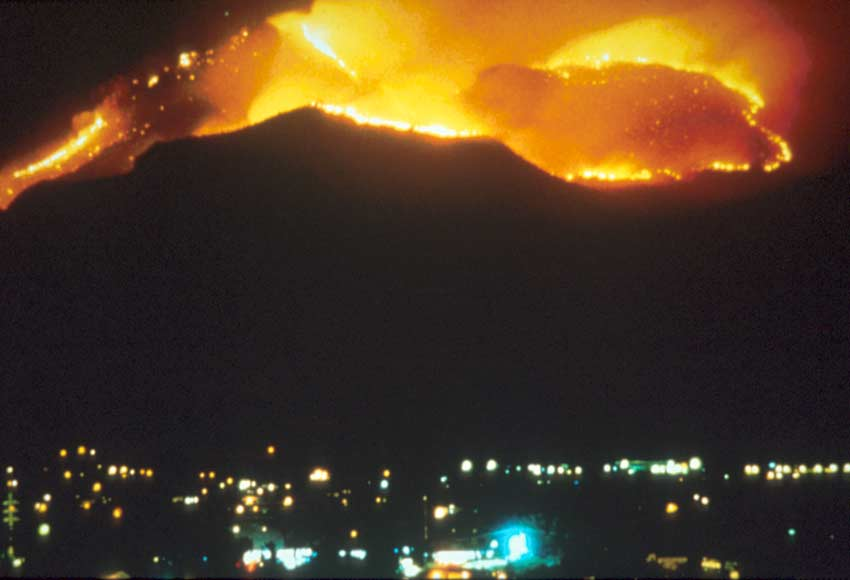 A night view of large wildfire spreading across a hillside directly above a small town.
