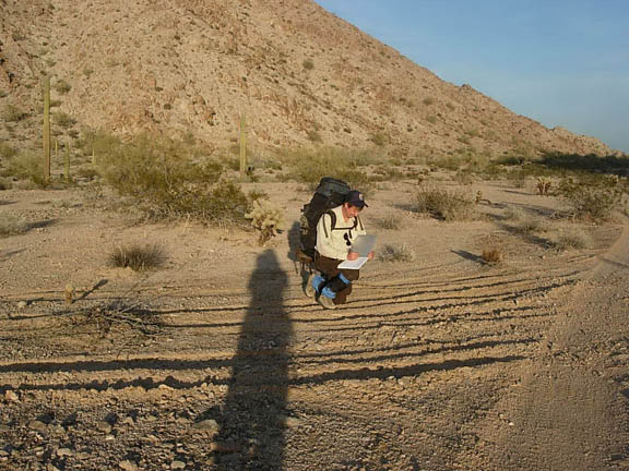 A backpacker records fresh vehicle damage. The damage is tire tracks that scar the desert floor. This was the purpose of the hike, to record all instances of disturbance to the wilderness from recent human activities.