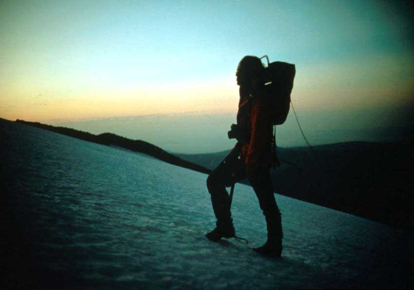 A lone hiker, on a large snowfield, silhouetted against an evening sky.