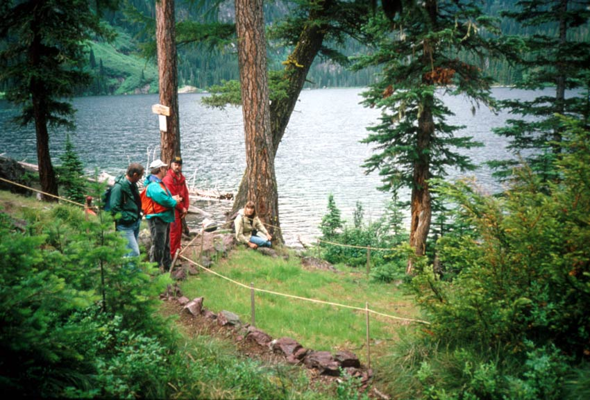 Several visitors walking a small forest trail, near the edge of a large lake.
