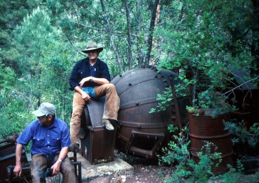 Two men sitting on old mining equipment abandoned in the dense green forest.