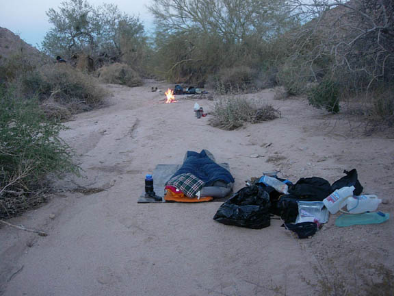 Backpackers set-up camp in a wash at the north end of the Sierra Pinta mountains. A small fire burns in the far end of the photo.