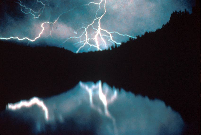 A mysterious image of lightning tearing across a cloudy sky at night, reflecting off the placid water of a small lake bordered by black trees.