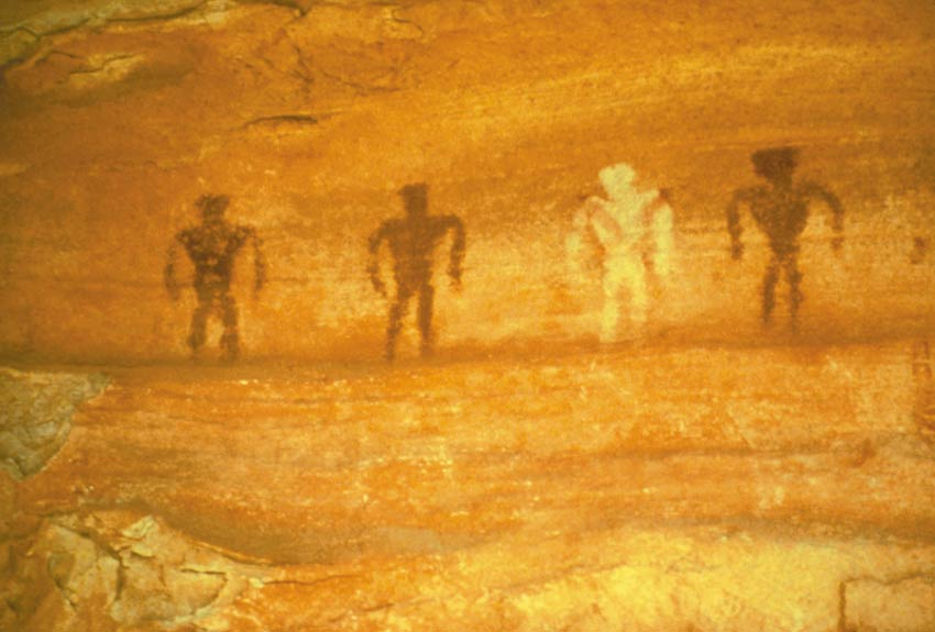 Ancient painting on a rock face, of four people, three black and one white.