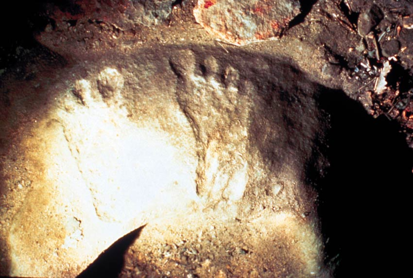 A close-up of two ancient footprints on the stone floor of a cave.