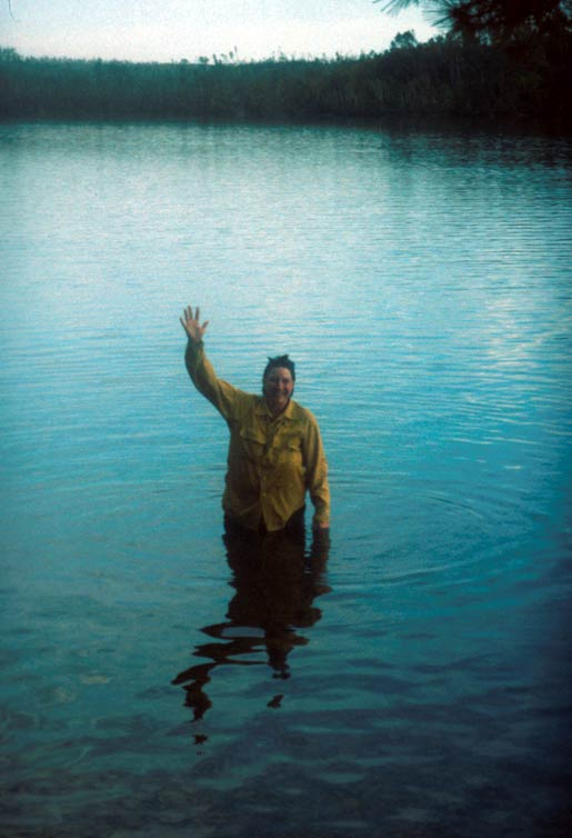 A man in a yellow shirt, standing waist-deep in a small lake.
