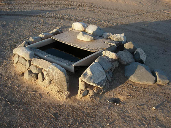 A box housing water sits on the ground. The box is secured on the ground by large rocks and it is intended for wildlife to use in times of drought.