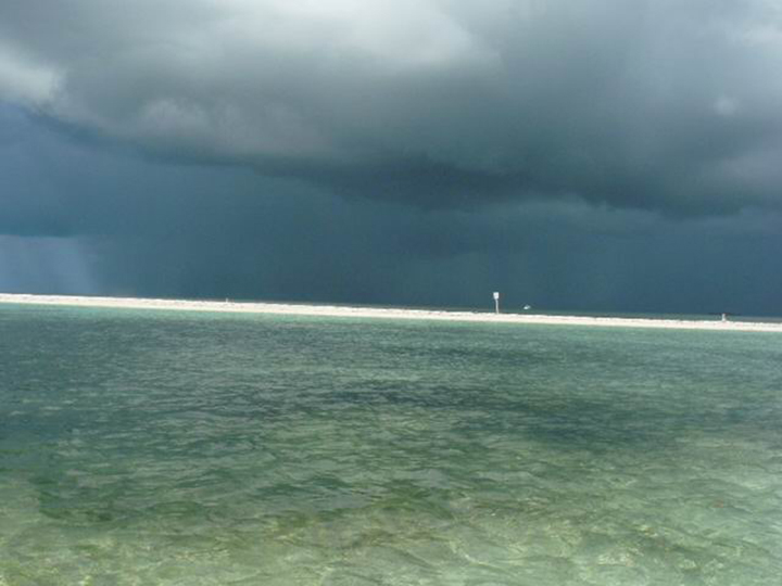 A thin strip of white sand separates blue green water from a large storm cloud above.