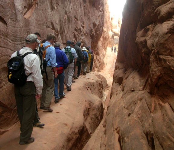 A cluster of hikers along a narrow path in the Arches National Park is an example of crowding.