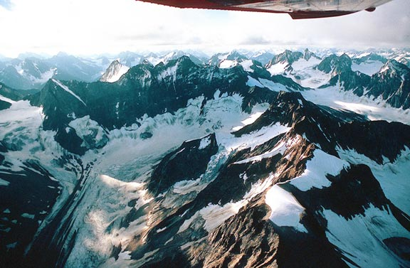 An aerial view of a jagged mountain bowl emptying a large glacier into the valley below, surrounded countless peaks in the distance.