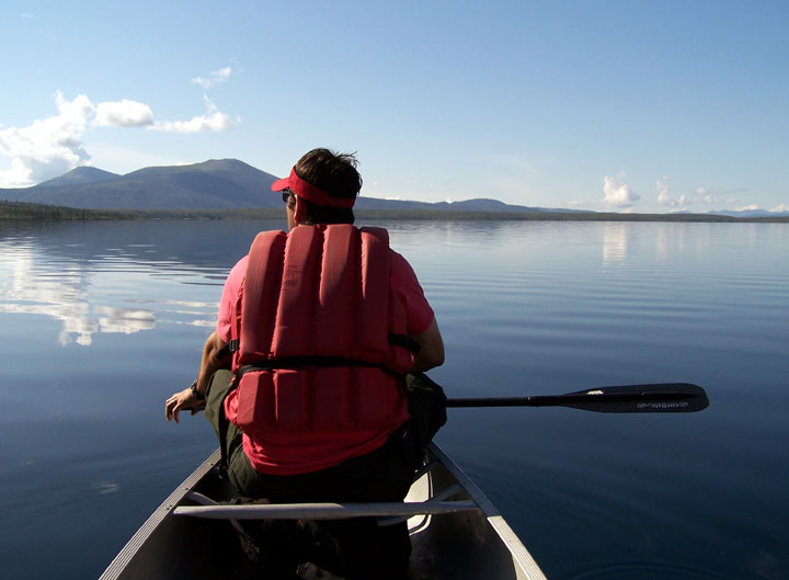A lone canoer rests his paddle, while viewing out over the reflection of the sky on the placid waters.