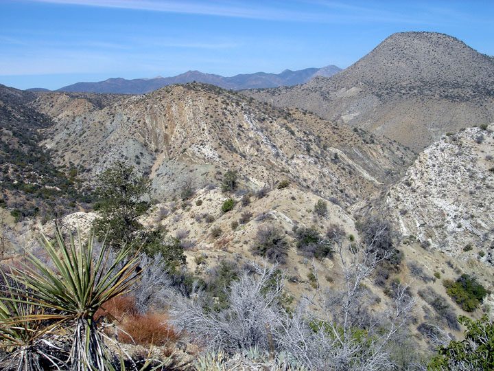 Viewing out over the rolling hills and small mountains of a dry desert landscape.